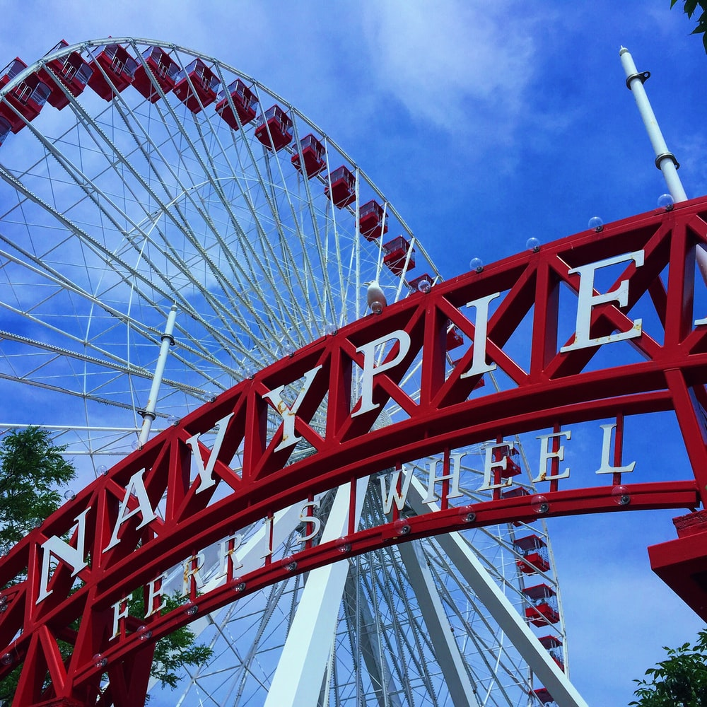 red and white ferris wheel under blue sky during daytime