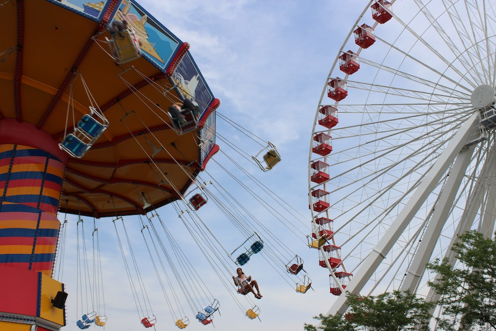 people riding on amusement park ride during daytime