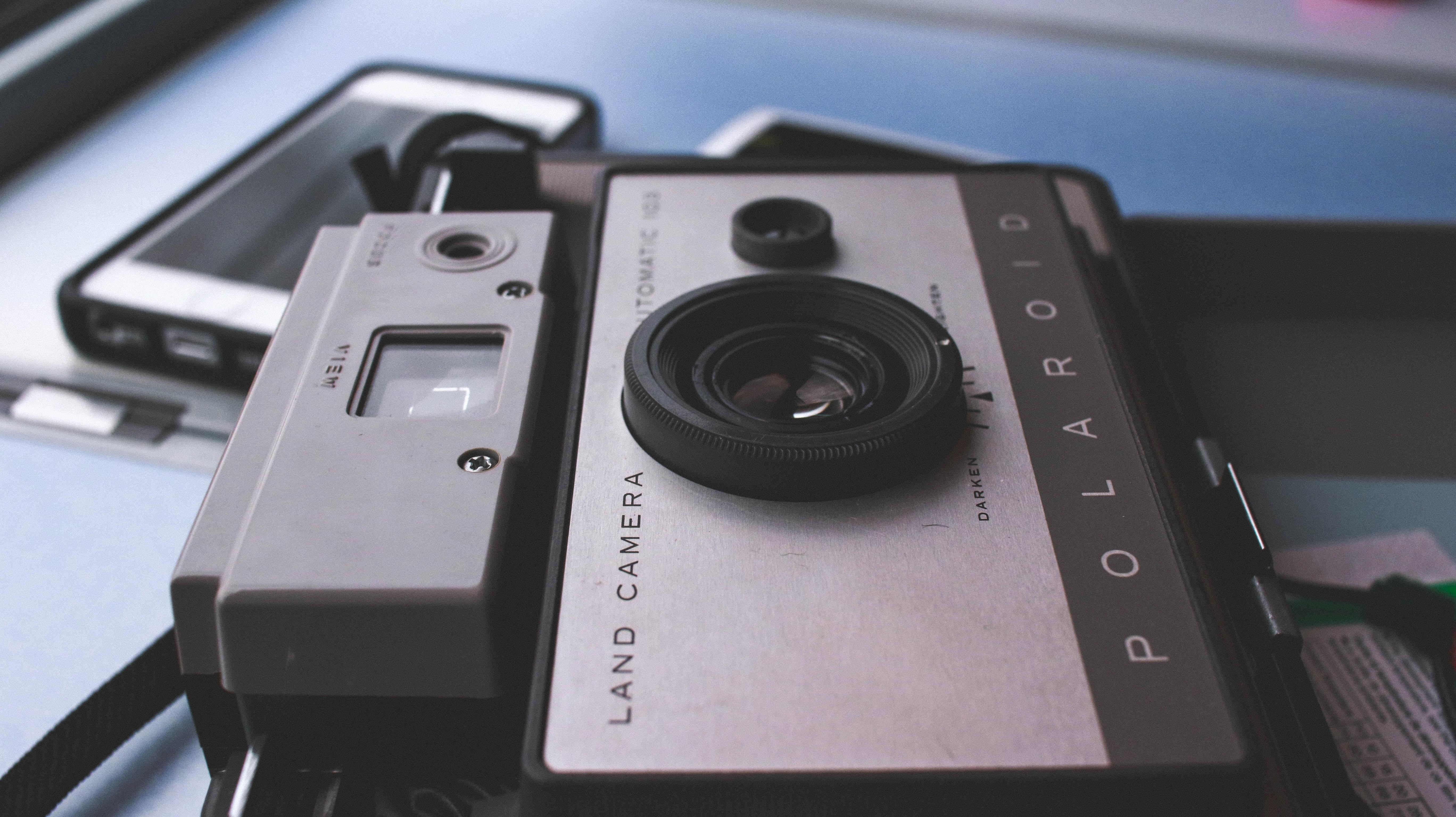 Macro of vintage polaroid camera on surface near iPhone mobile phone