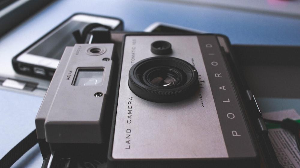 gray Polaroid land camera on table near white Android smartphone