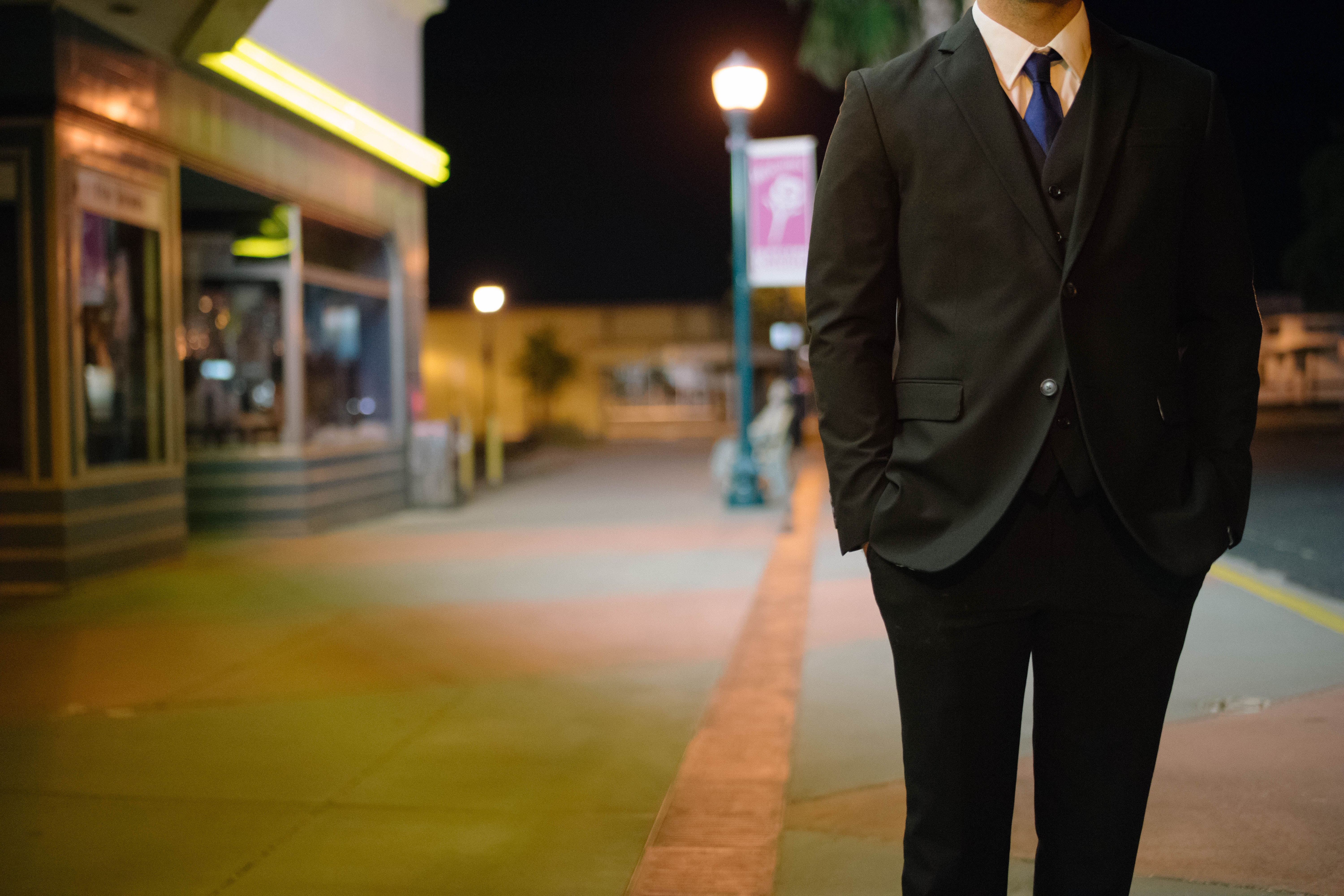 A man in a black suit standing in the street with his hands in his pockets