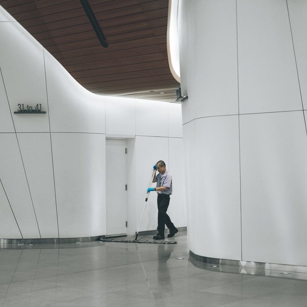 man cleaning on floor beside white wall