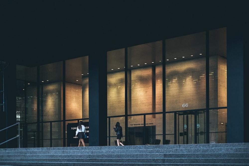 two woman walking near clear glass wall