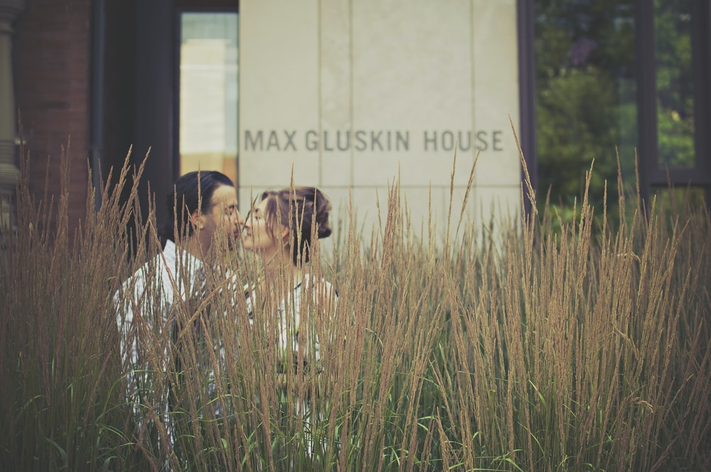 woman and man kissing near Max Gluskin House building
