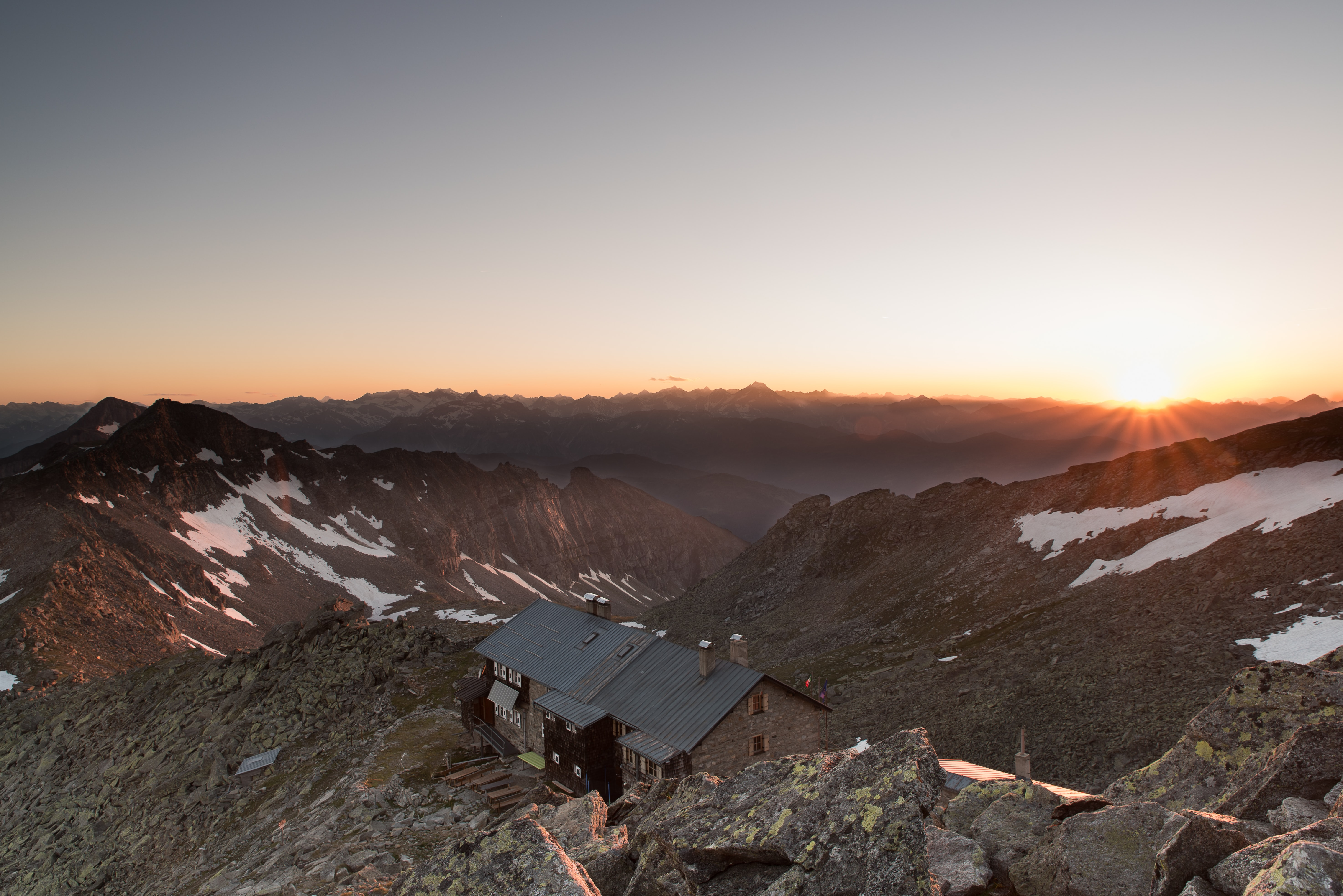 Sun setting overlooking a house surrounded by snow covered mountain tops.