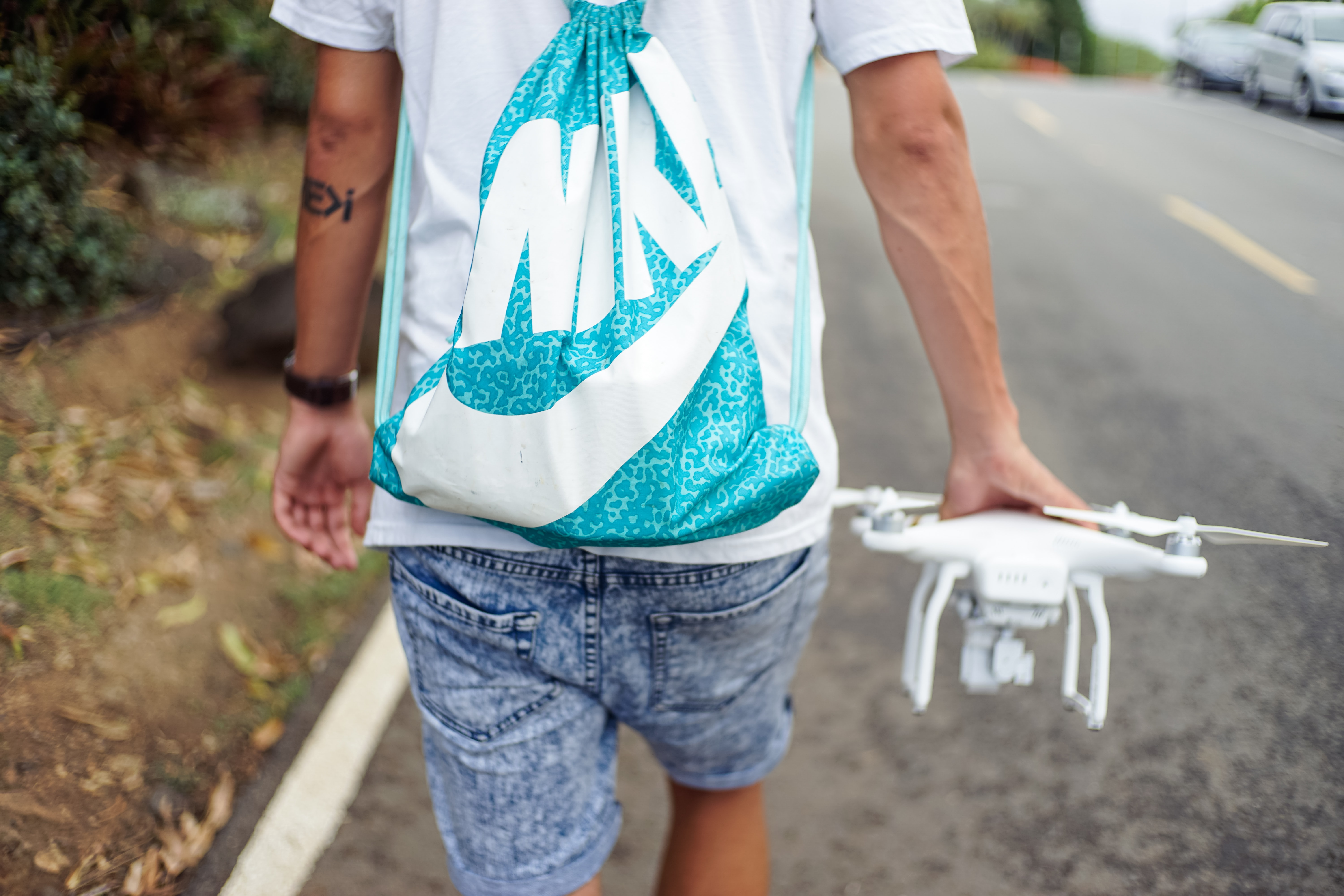 man holding white R/C quadcopter while walking beside concrete roadway