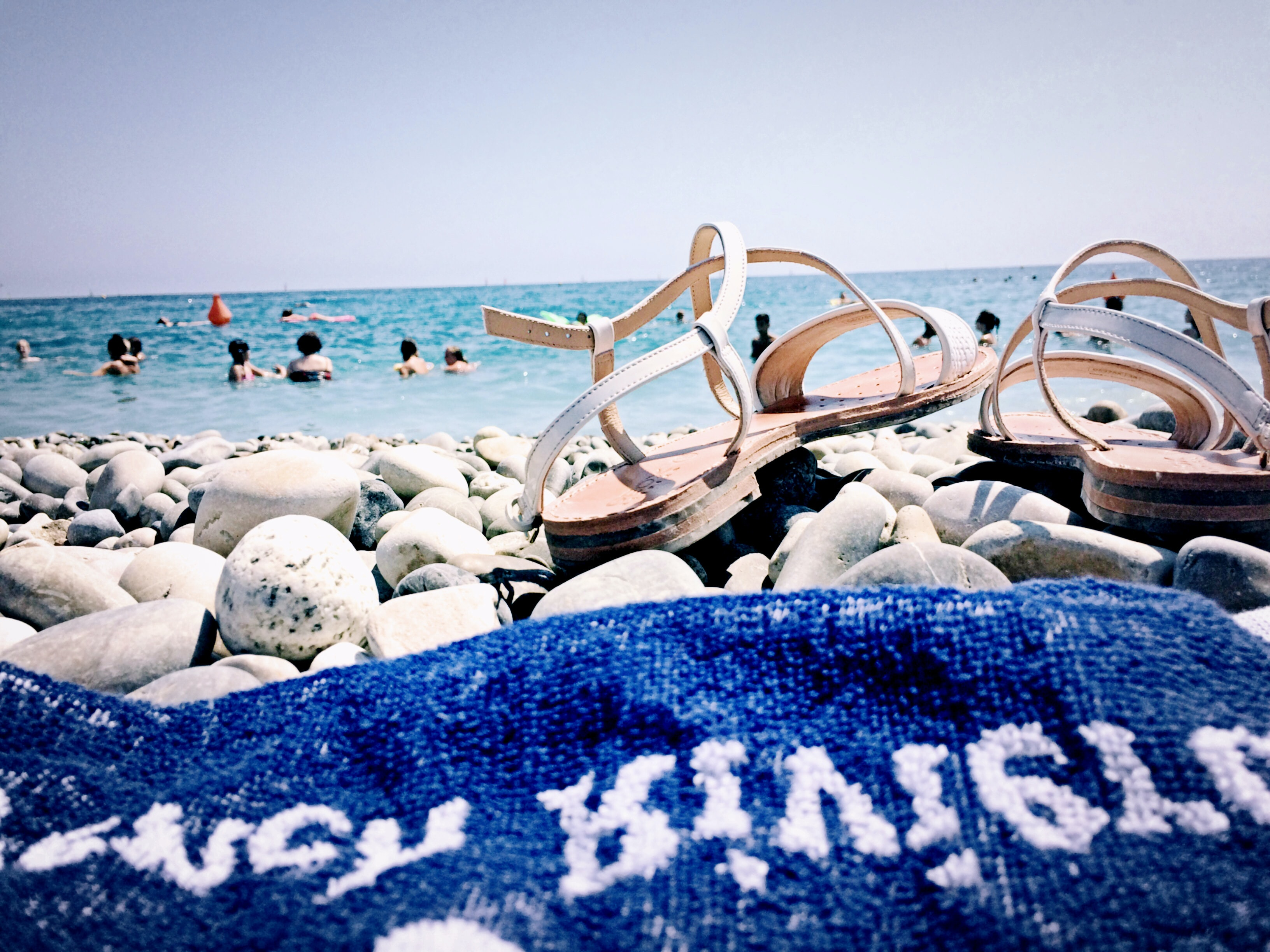 A close-up of a blue towel and a pair of sandals on a rocky beach