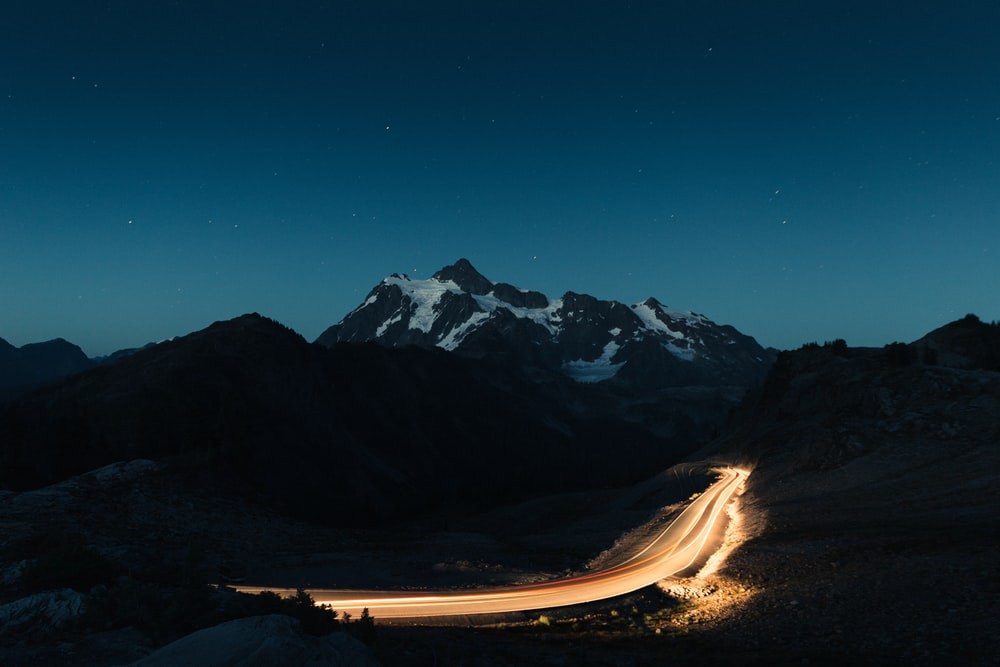 snow covered mountain under blue nightime sky