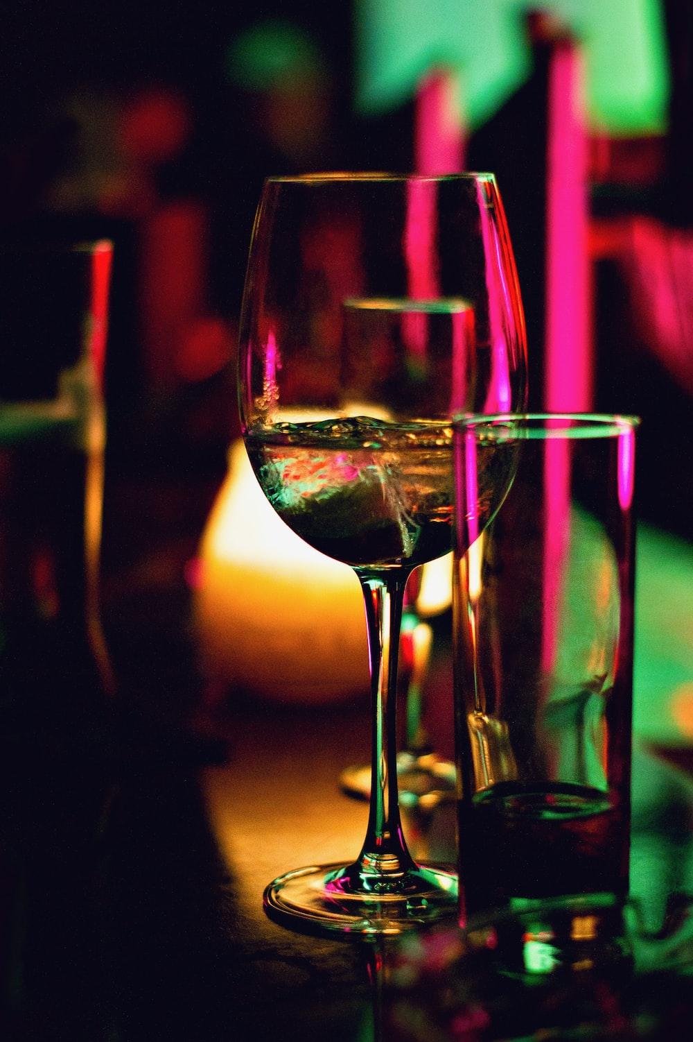 half filled wine glass beside half empty clear pint glass