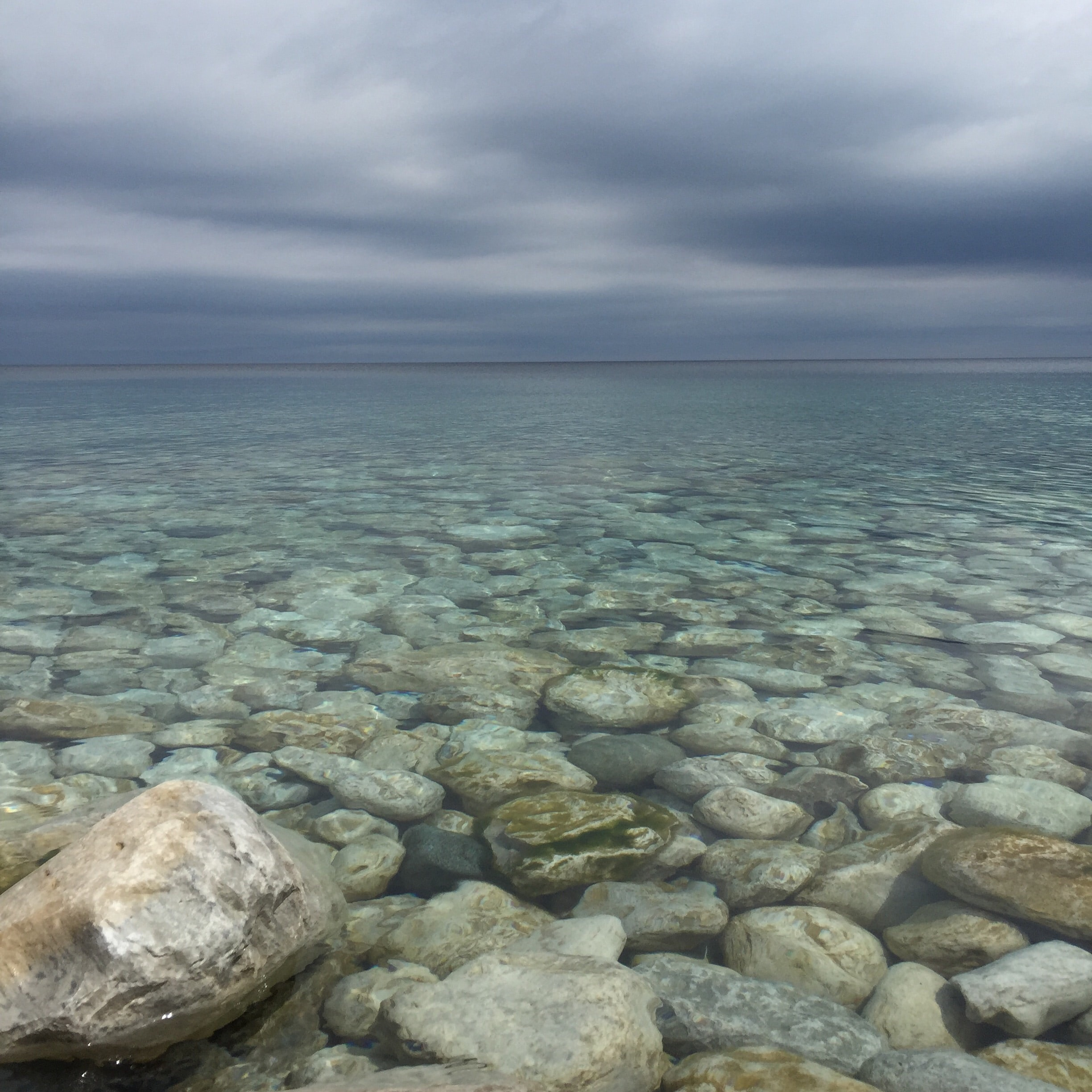 body of water with stones under cloudy sky