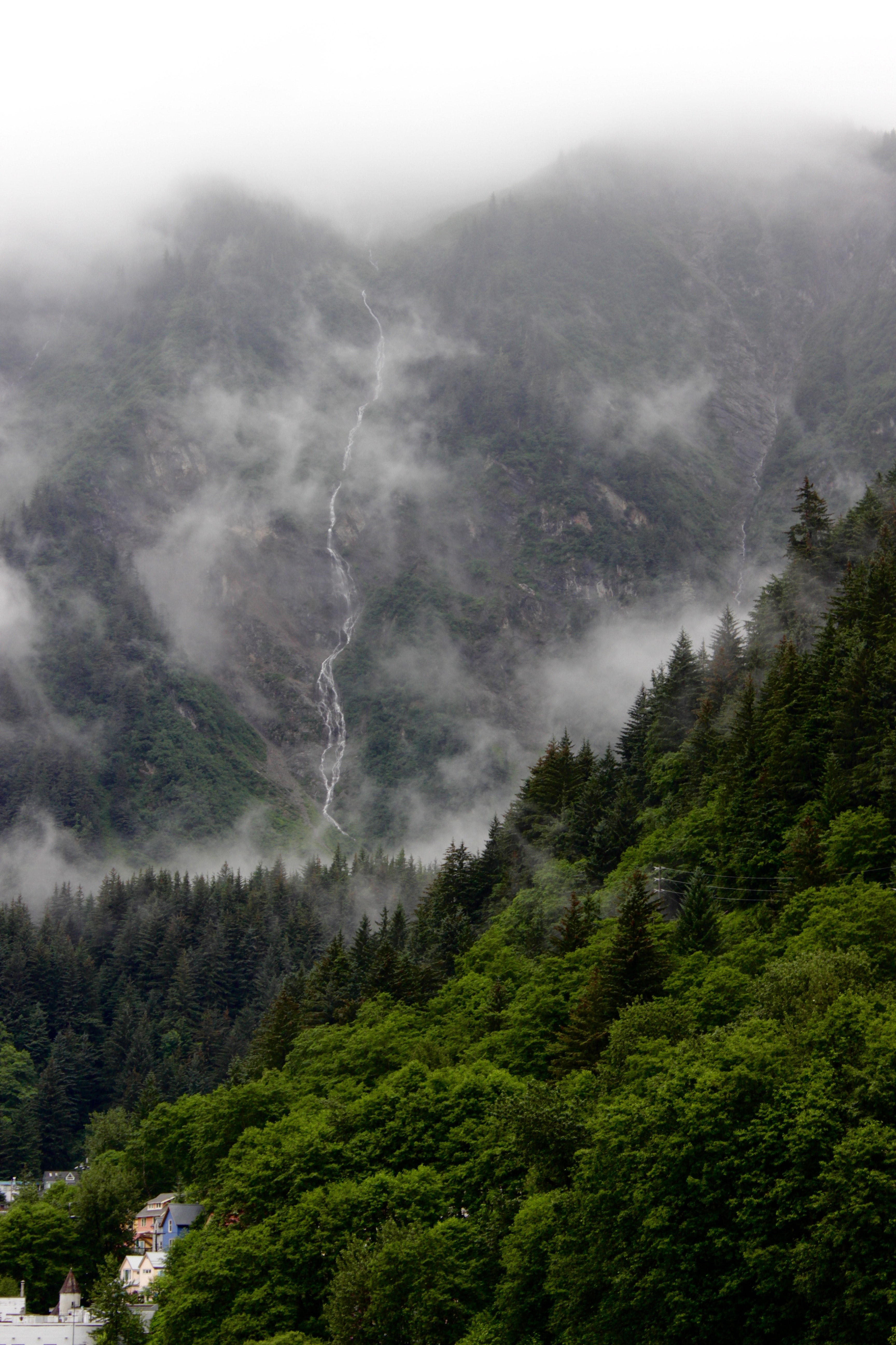 A narrow waterfall pouring down a tall mist-shrouded mountain in Alaska