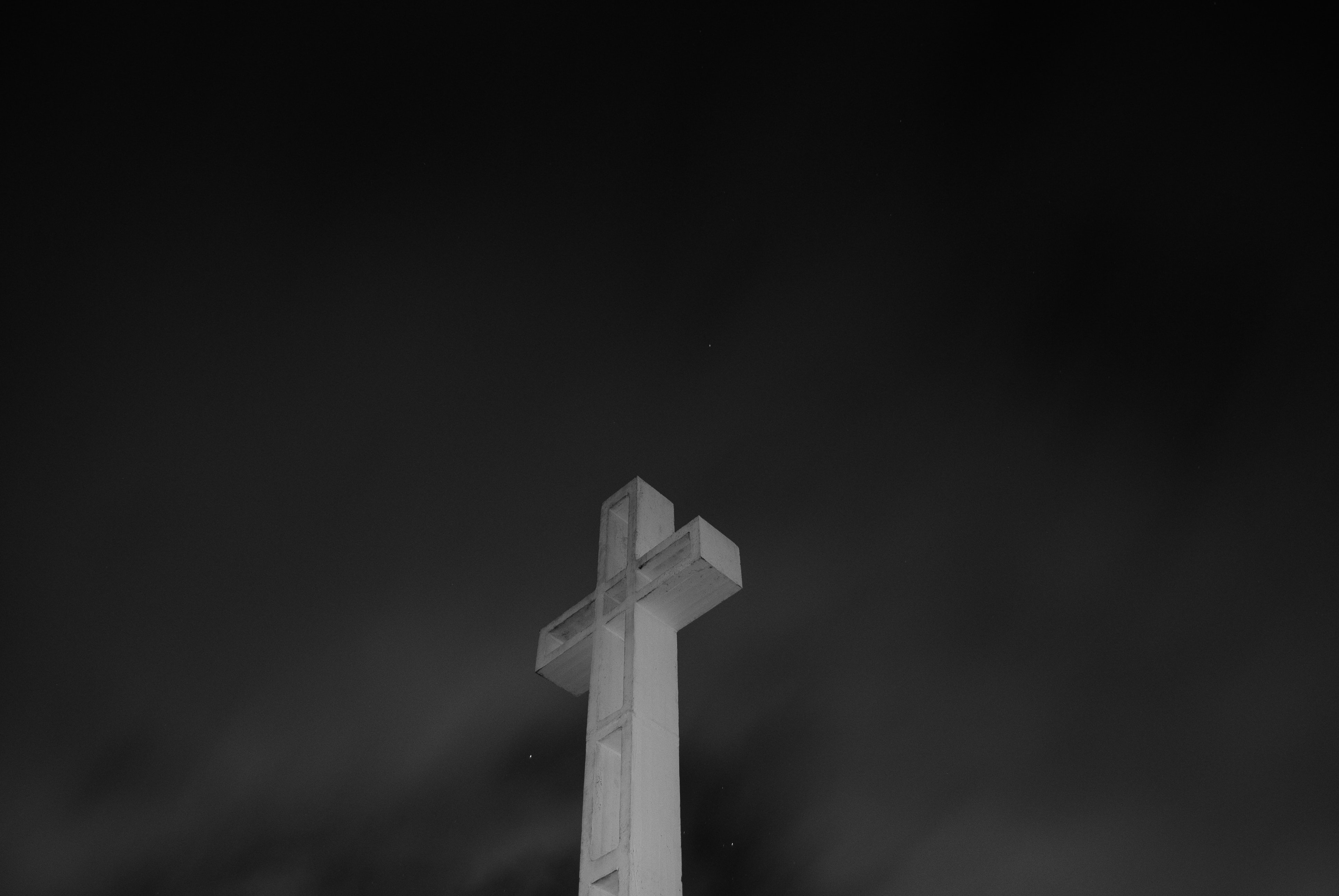 Black and white shot of white cross on Soledad Mountain on dark sky background