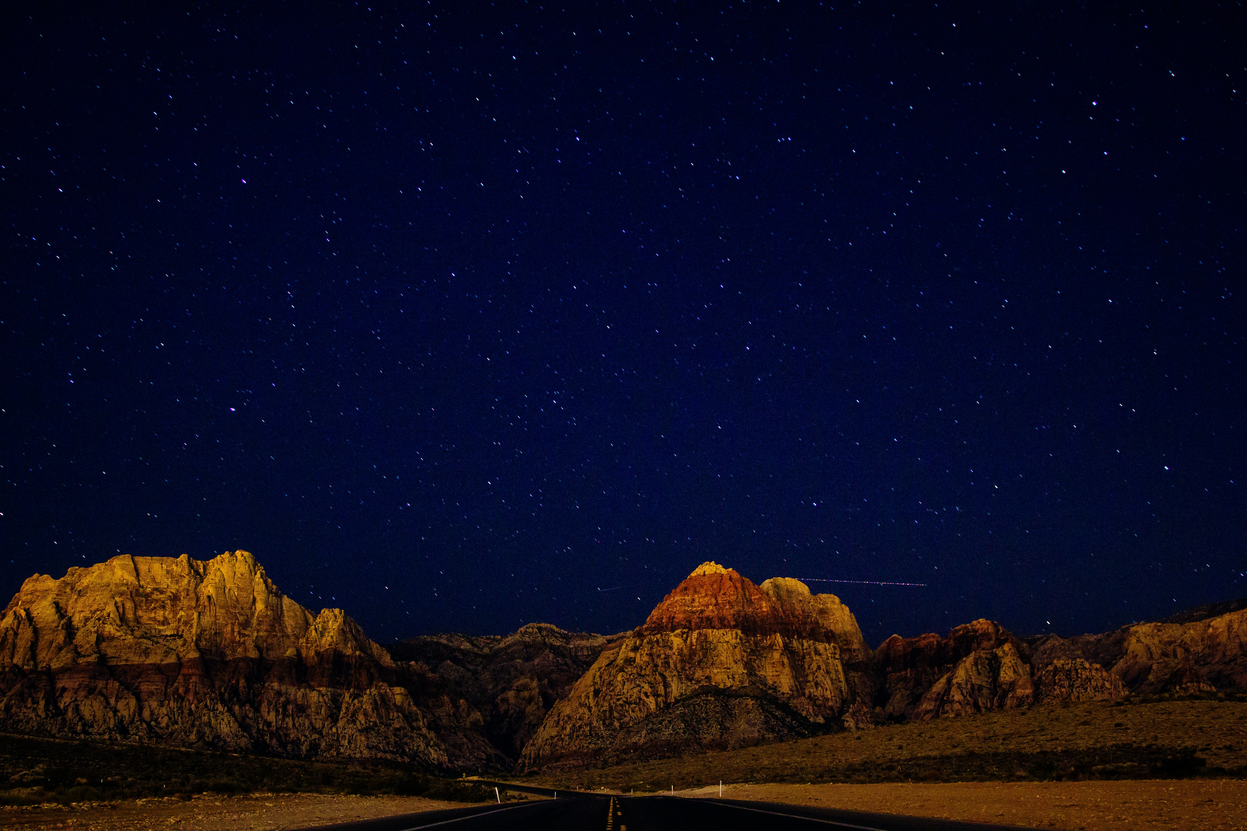 The deep blue sky full of stars over the hills and the road in Las Vegas.