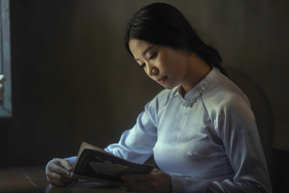 woman wearing gray long-sleeved tops reading book