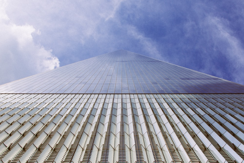 low angle photography of high-rise building under blue sky and white clouds