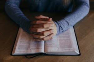 Man ber med händerna på uppslagen bibel