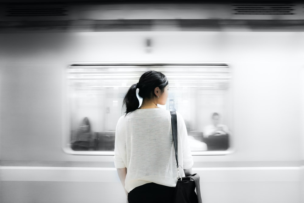 woman in white elbow-sleeved shirt standing near white train in subway