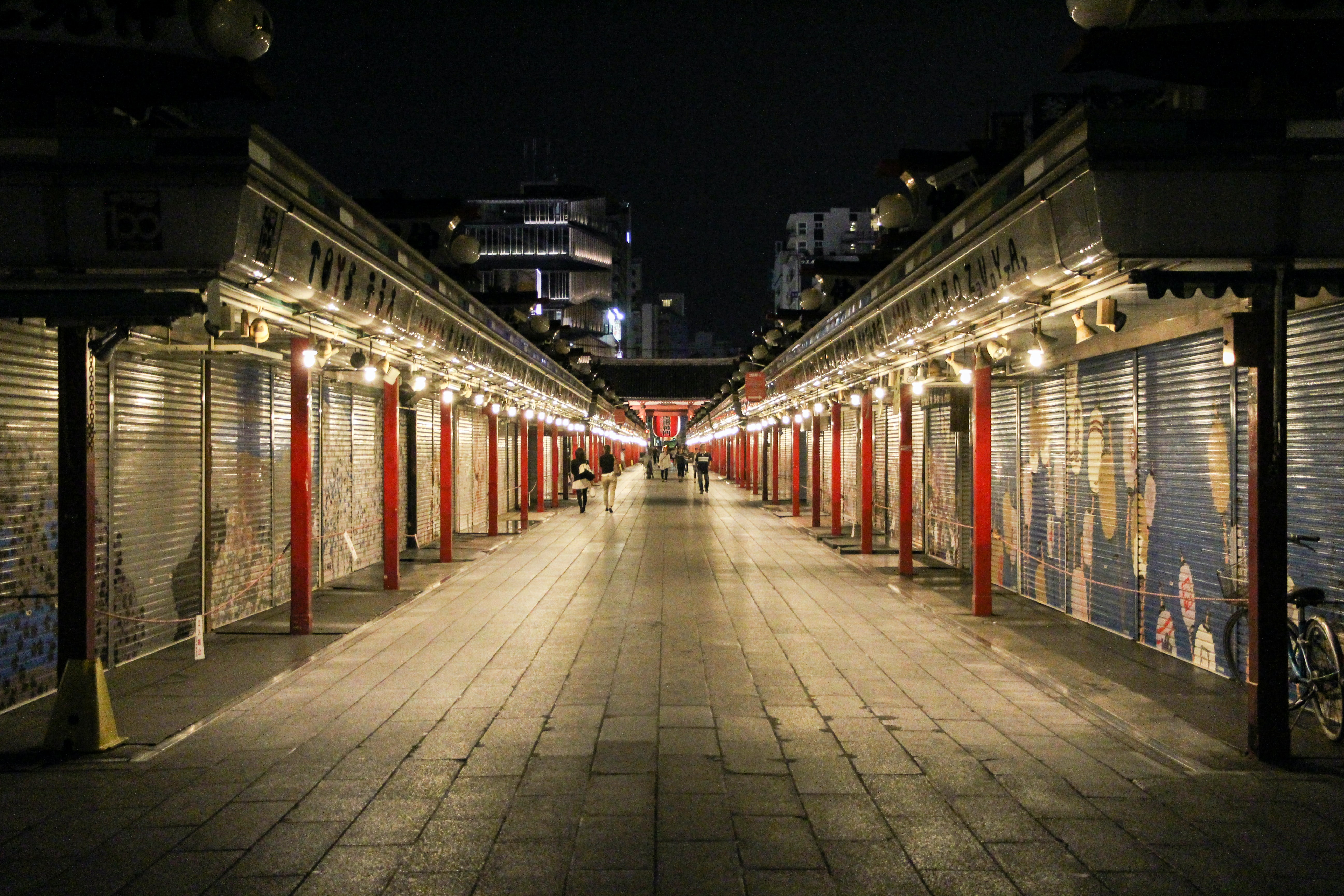 empty pathway beside stores with roll top doors at night time
