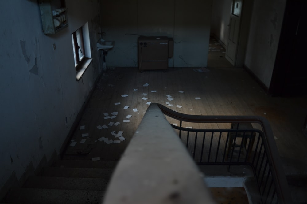closeup photo of concrete stair surrounded by white painted wall