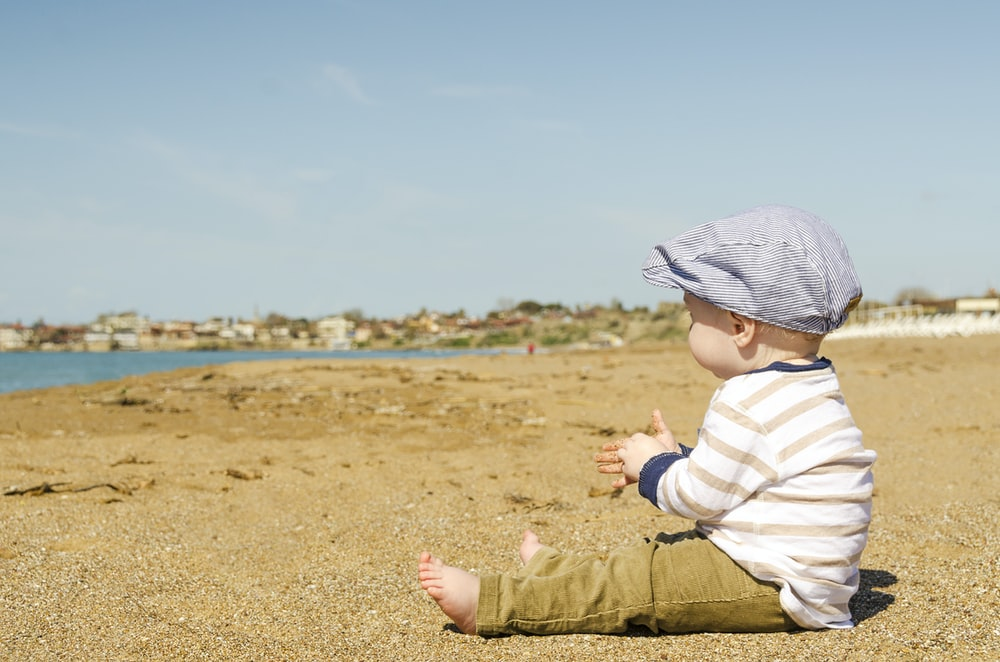 sitting toddler on seashore at daytime