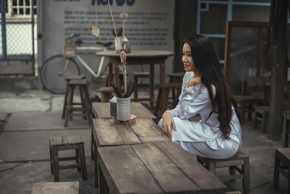 woman gray dress sitting on chair near table
