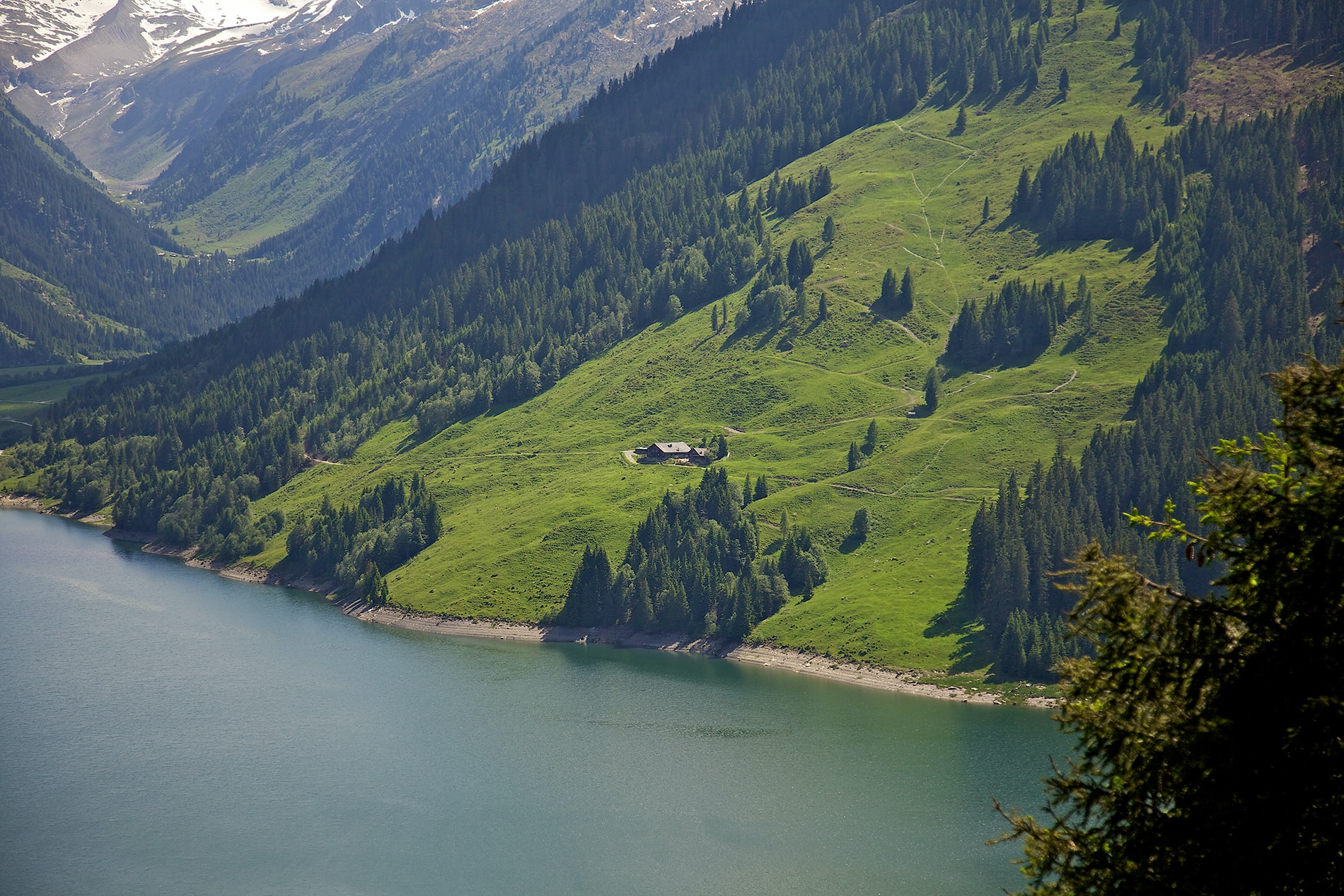 Small buildings on a green slope over a mountain lake