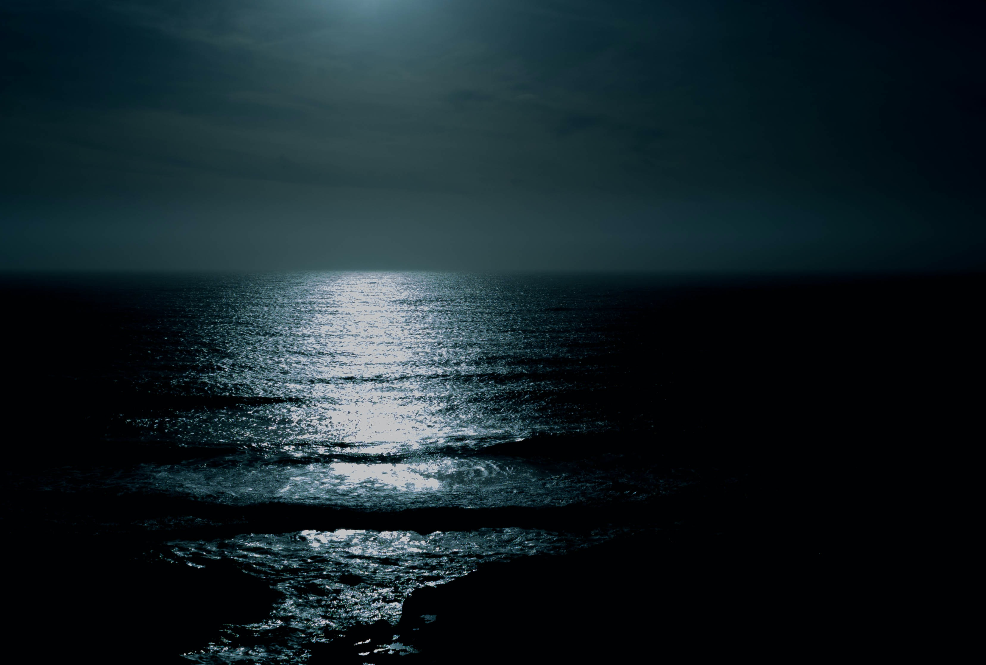 body of water under cloudy sky at night