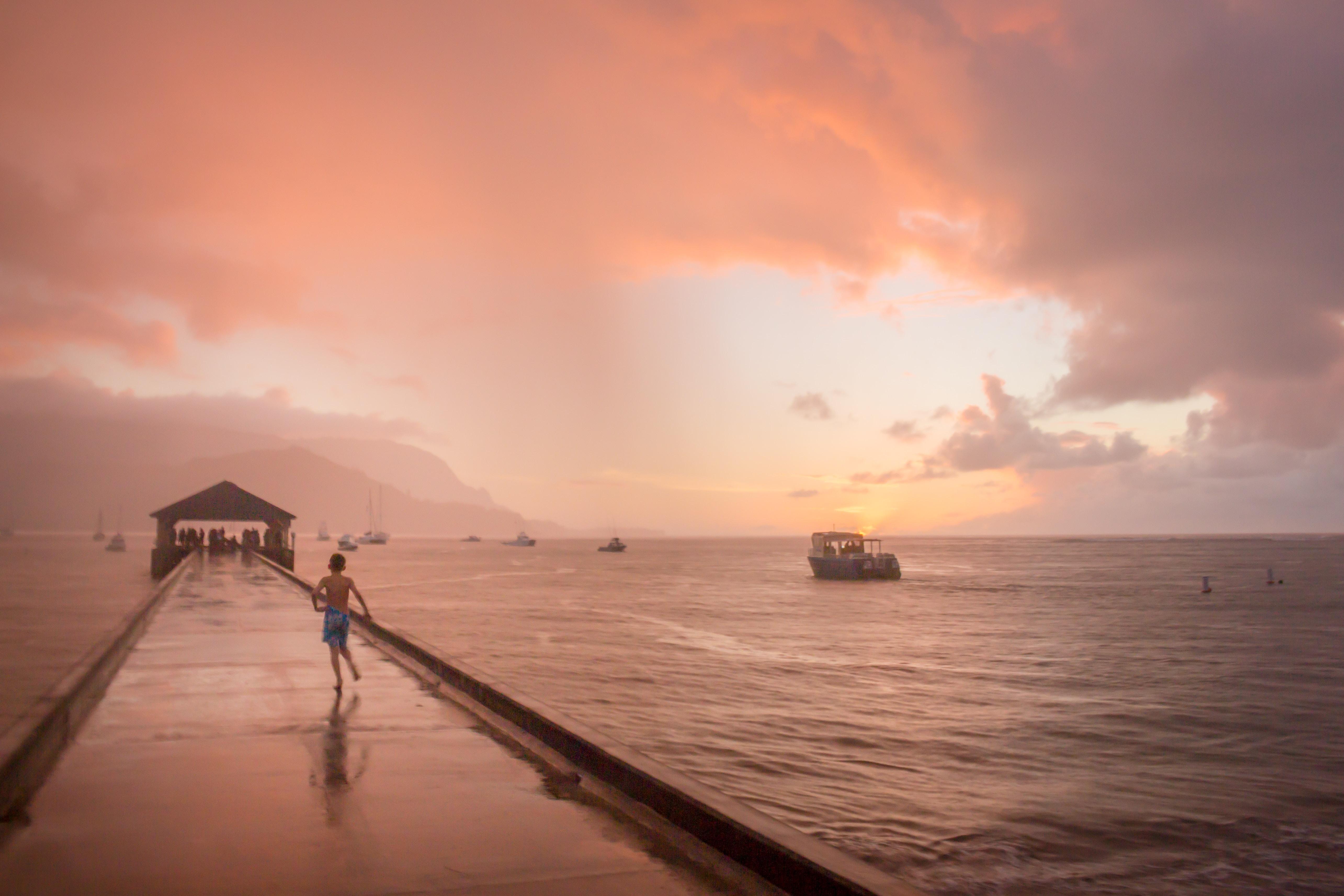 boy running on dock under cloudy sky