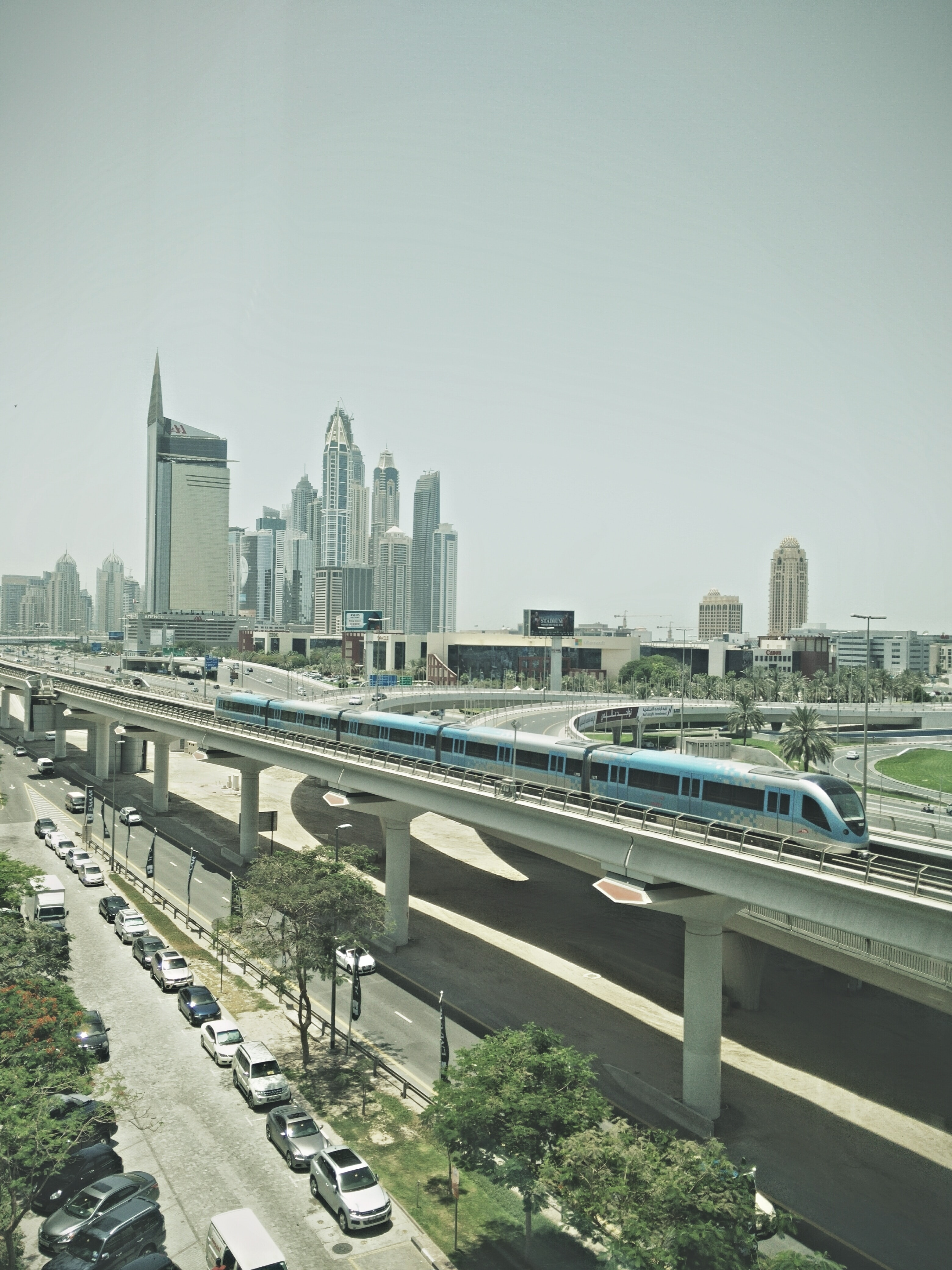 Train on bridge in Dubai with city skyscrapers in background and cars parked on pavement below