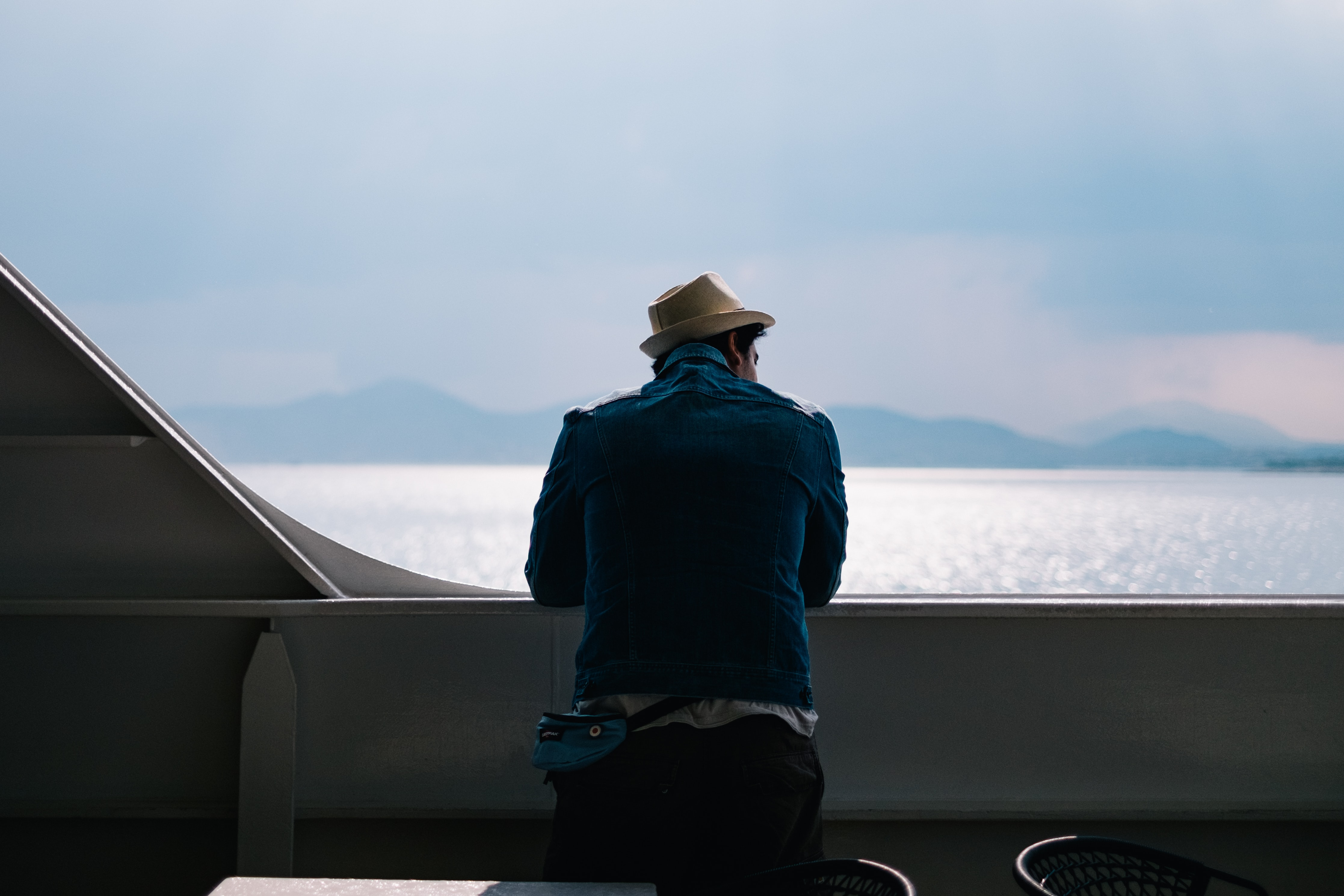 Man in a hat leans over the side of a boat on the water