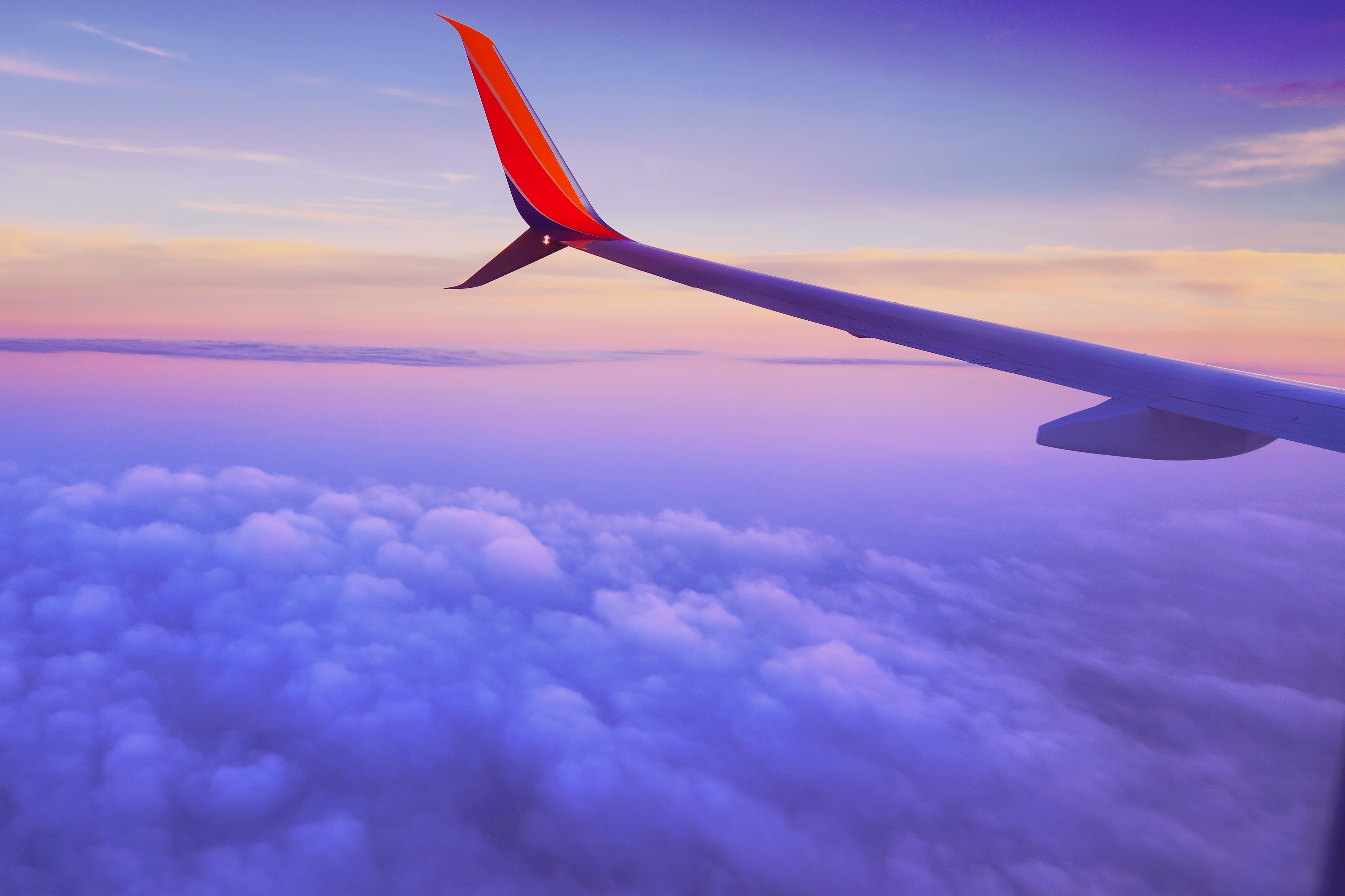 person in a plane flying at high altitude taking photo of left airplane wing during daytime
