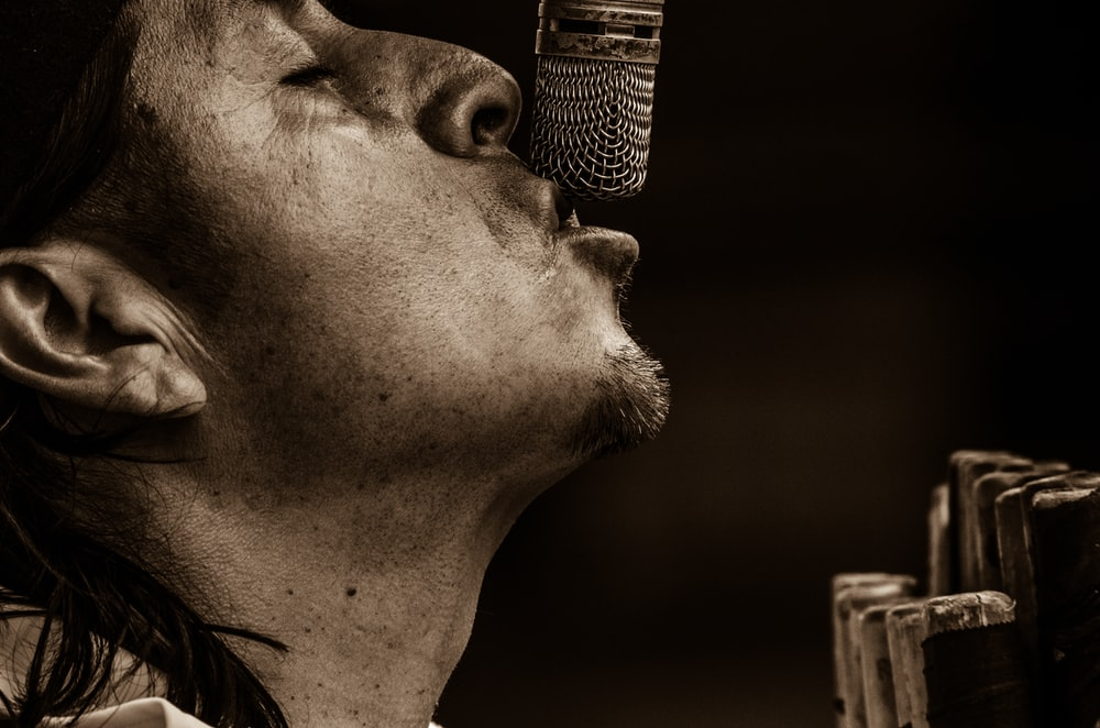 man singing with microphone grayscale photography