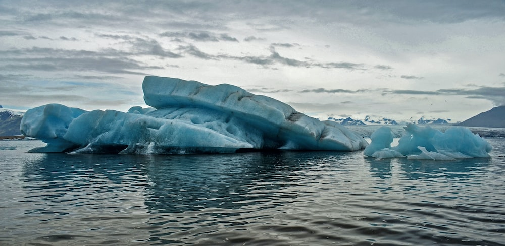 body of water with iceberg under cloudy sky