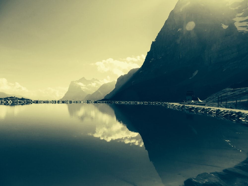 low-light photo of calm body of water in front of mountain