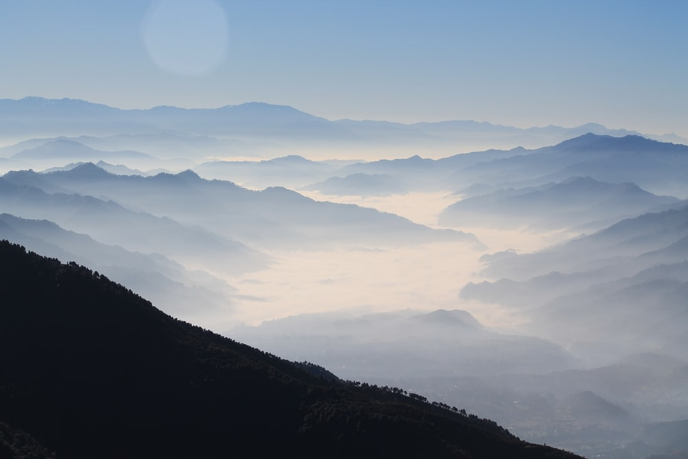 aerial photography of mountain range covered in clouds at daytime