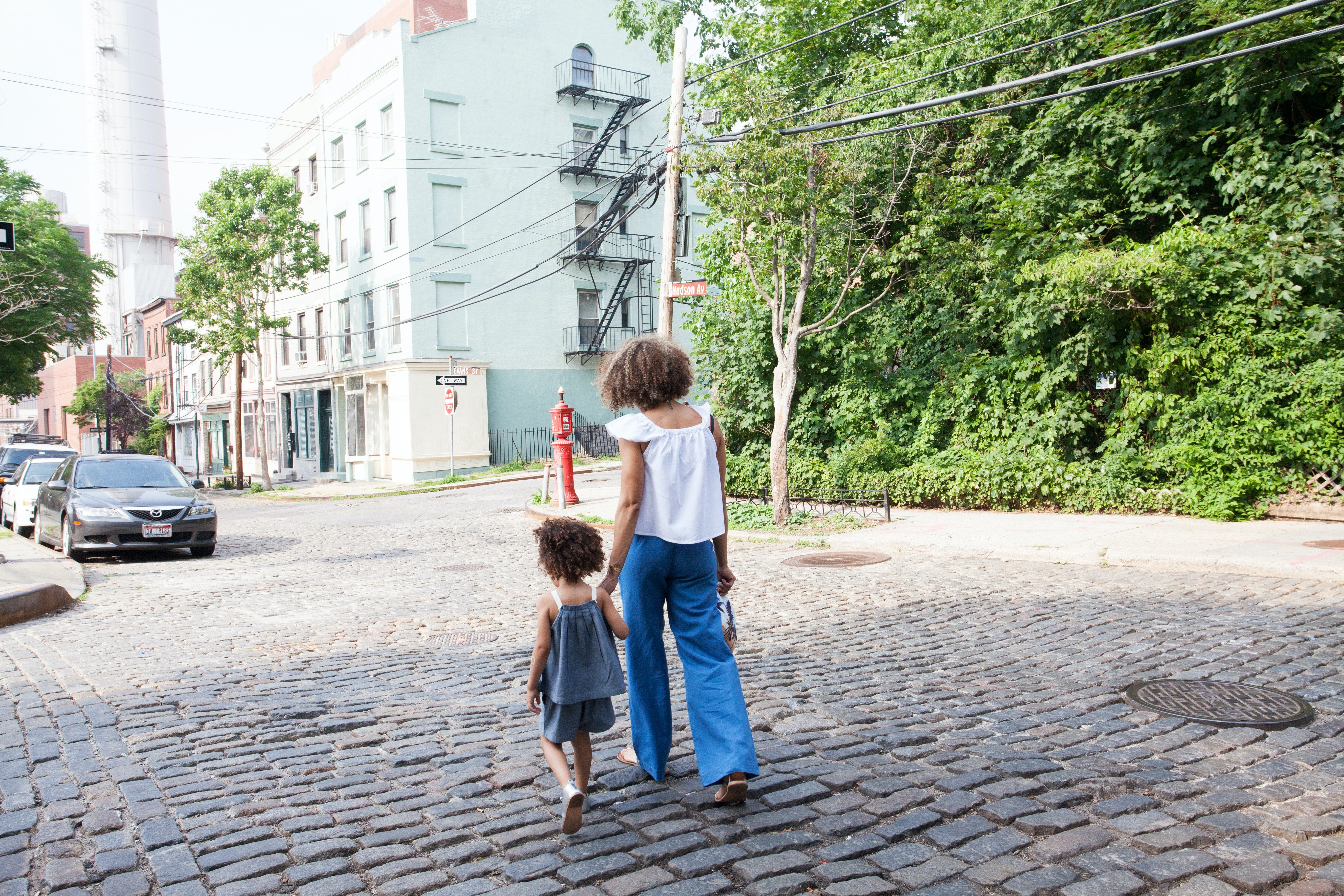 woman in white cap-sleeved shirt and blue pants walking beside girl in gray tank top