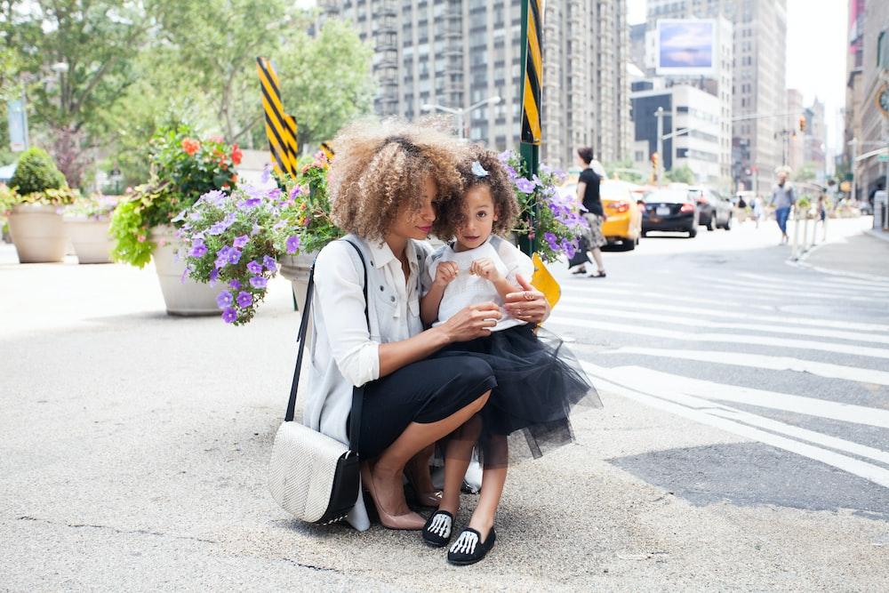 woman in white dress shirt holding her daughter in tutu dress beside of asphalt road during daytime