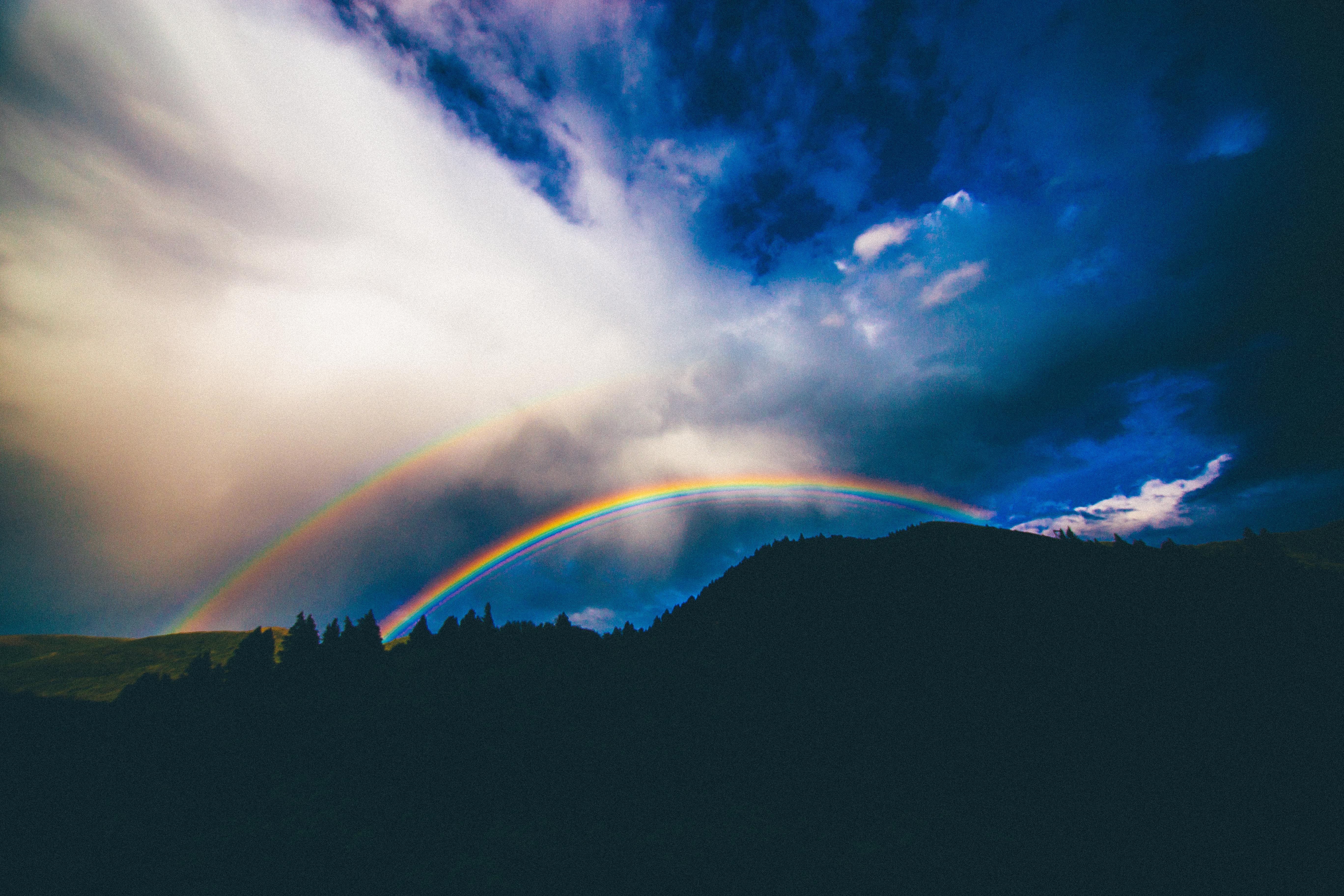 A mountain silhouette with a double rainbow in the blue sky in Provo