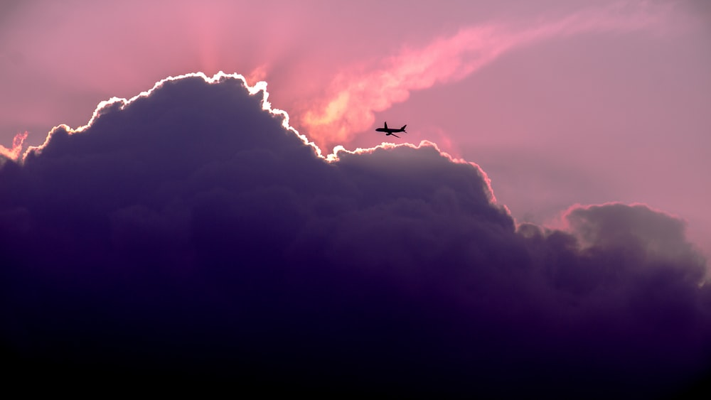 silhouette of airplanes of white clouds