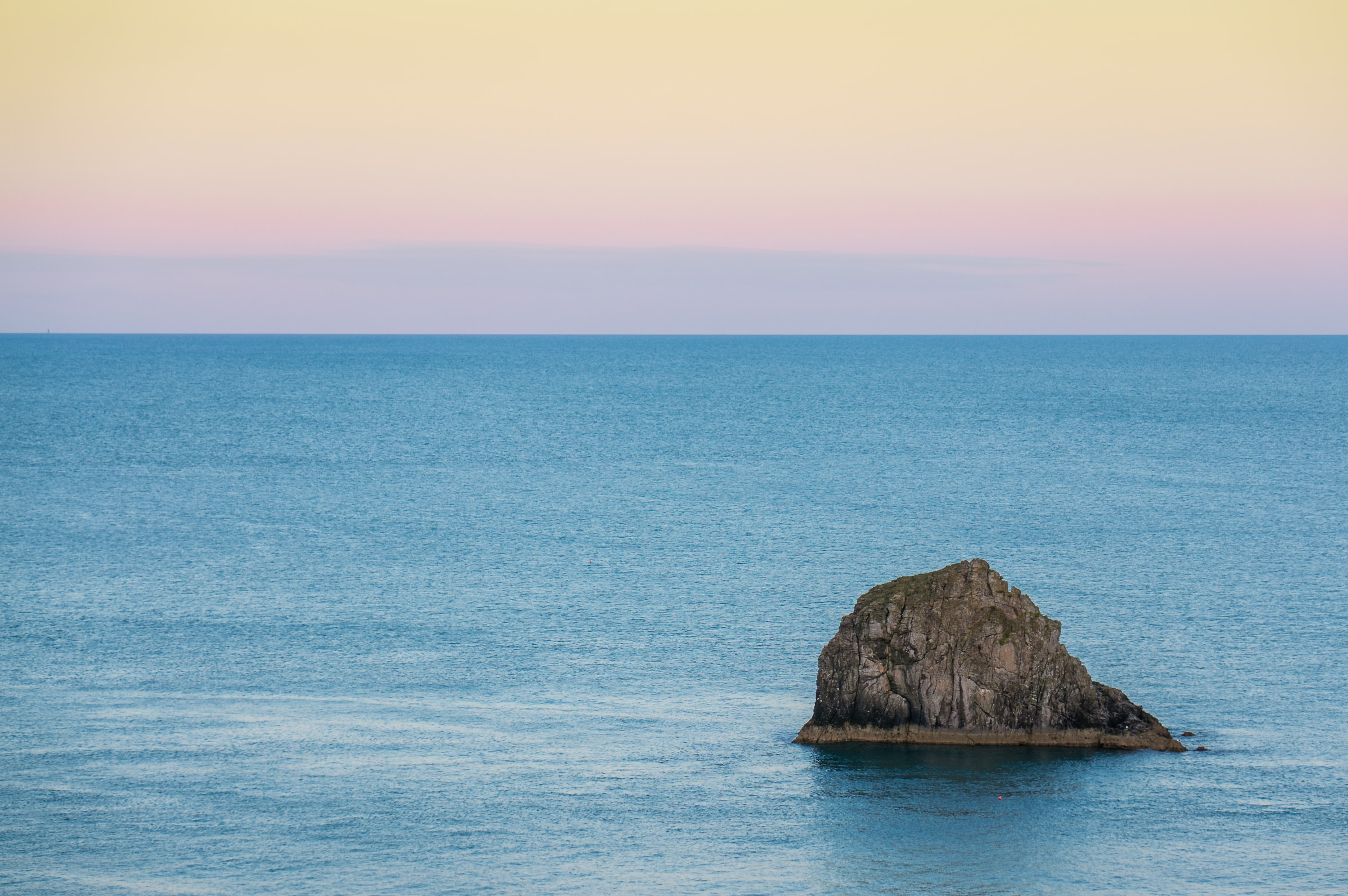 A lone rock formation protruding from the azure sea under a pale orange sky