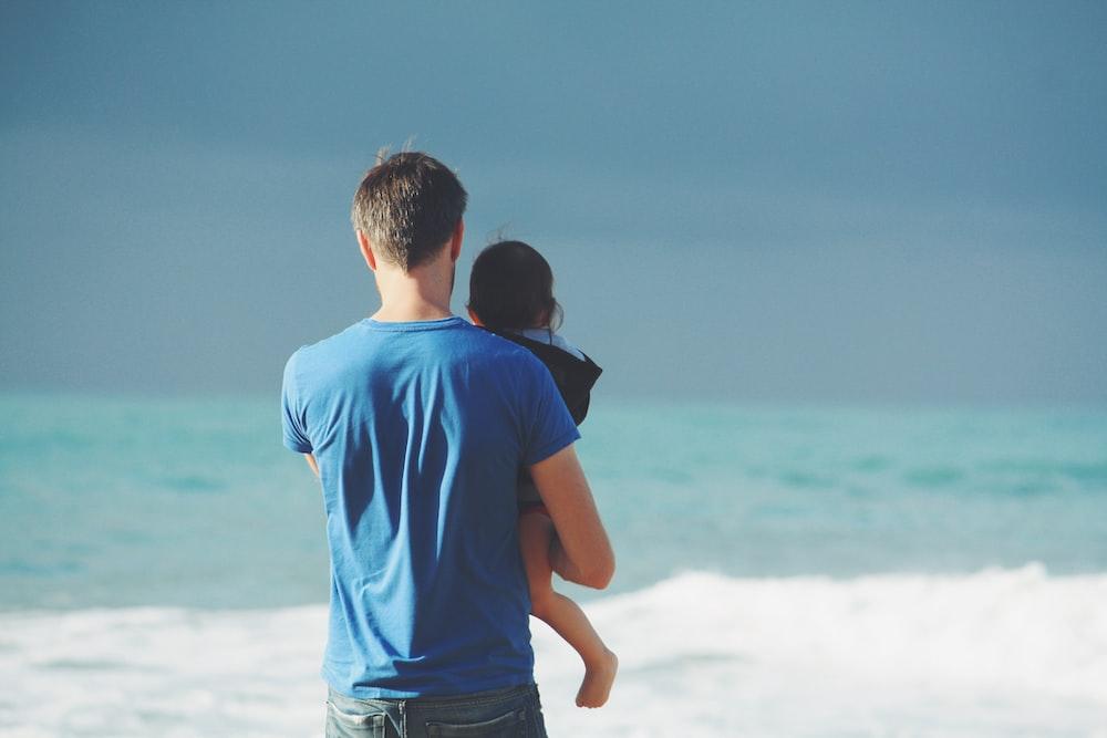 man wears blue crew-neck t-shirt holding toddler wears black hooded jacket near ocean under blue sky at daytime