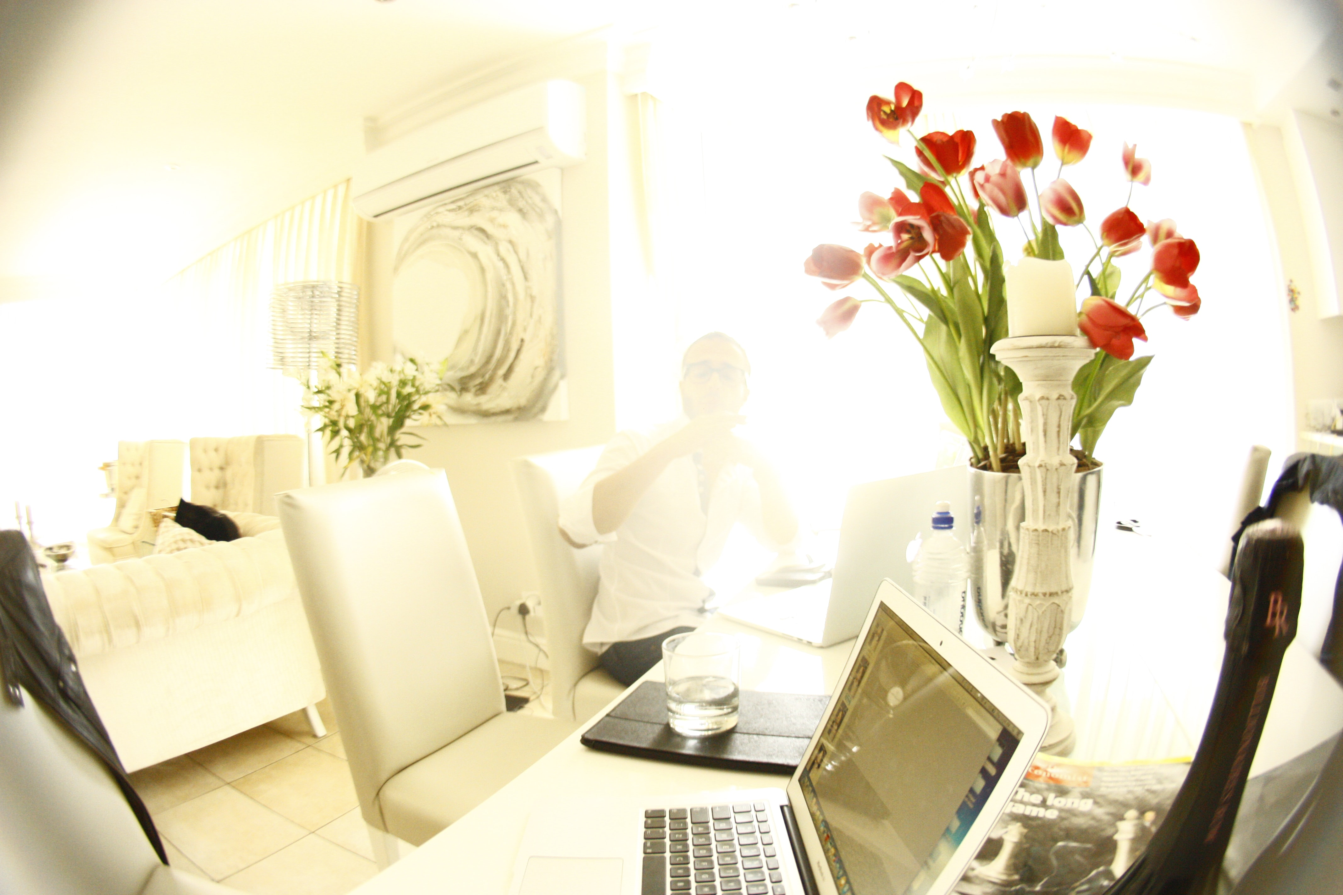 A laptop next to a vase full of red roses.