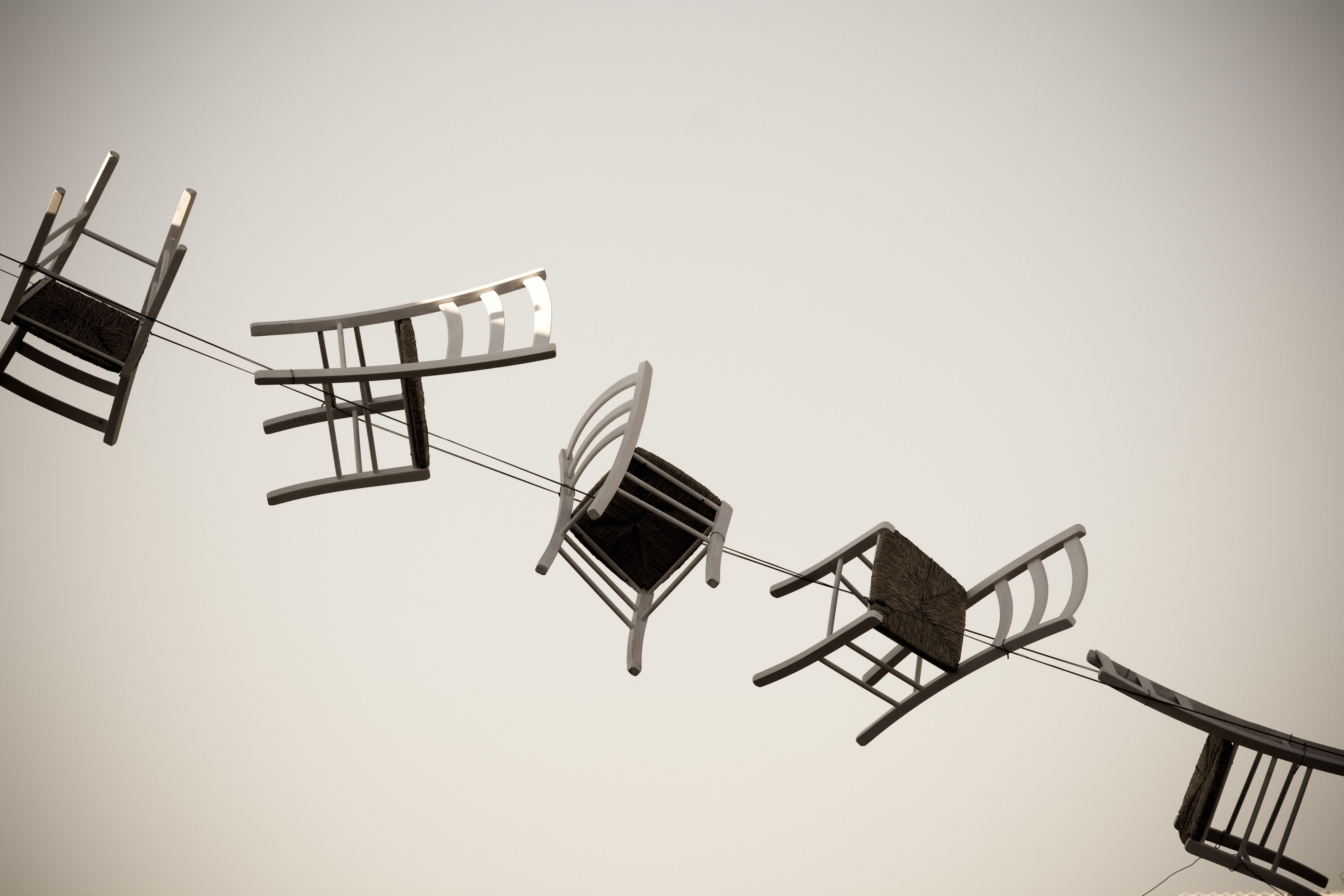 Suspended chairs on cable art design with light background in Otranto