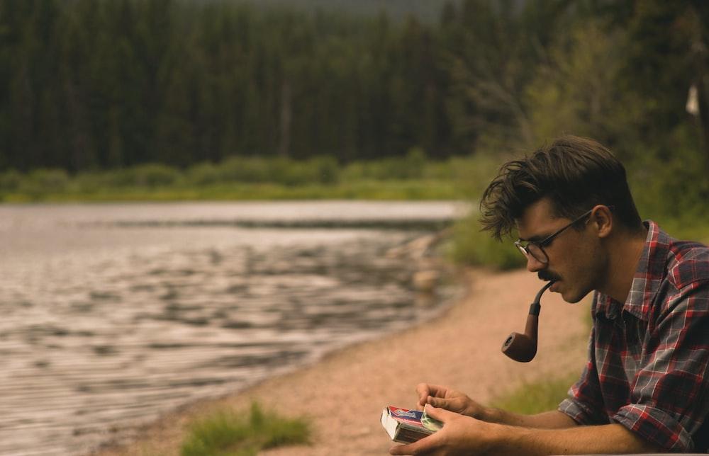 man smoking on pipe beside lake
