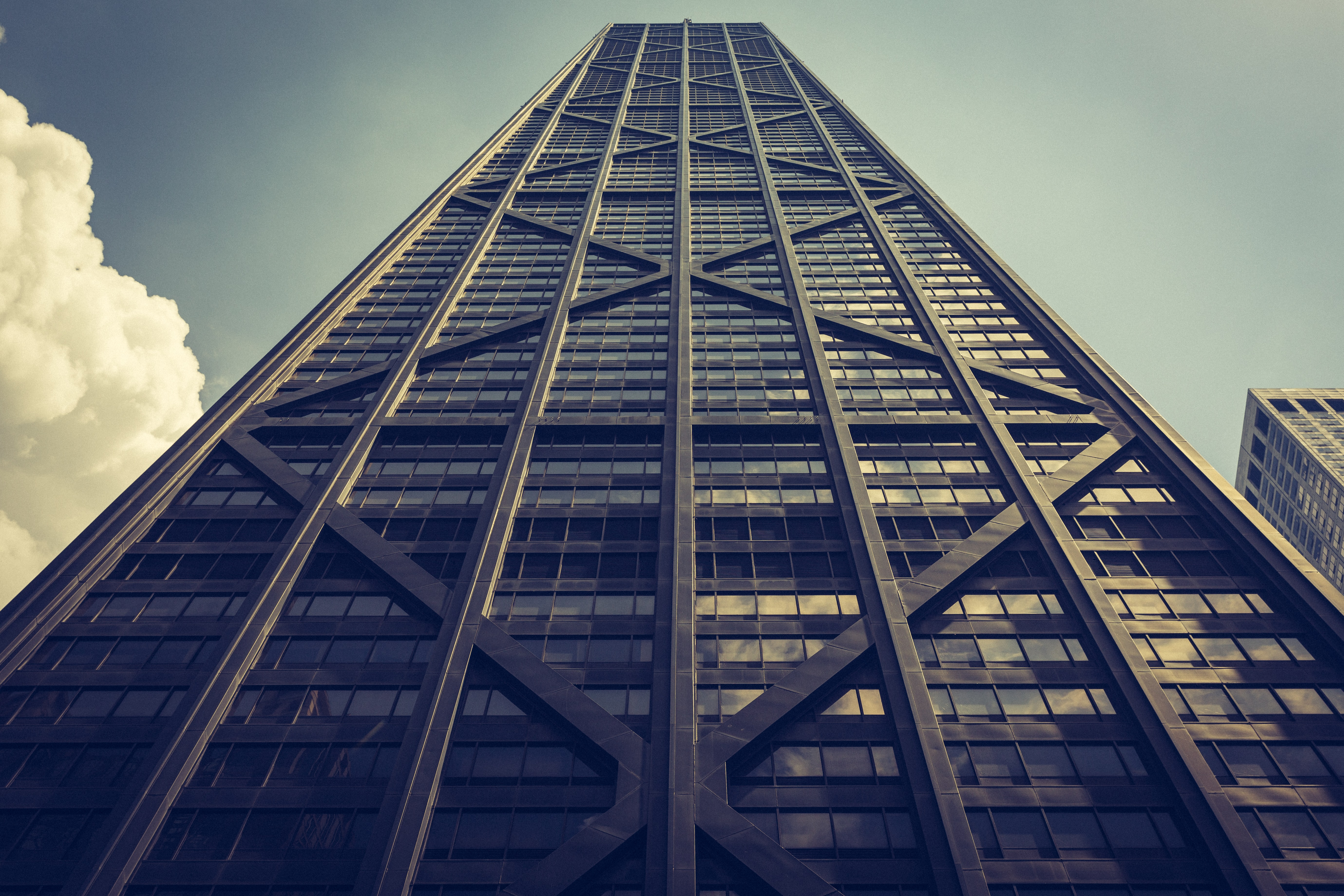 Looking up at a tall dark skyscraper with windows and diagonal and vertical lines
