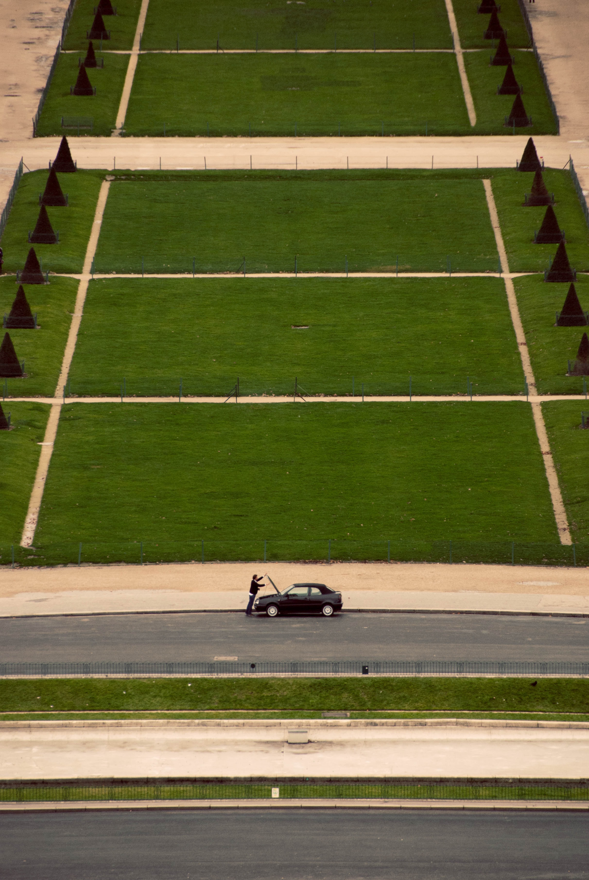 Man inspecting car parked in front of grassy fields