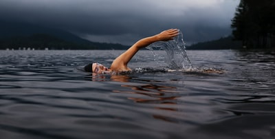 man swimming on body of water swimming teams background