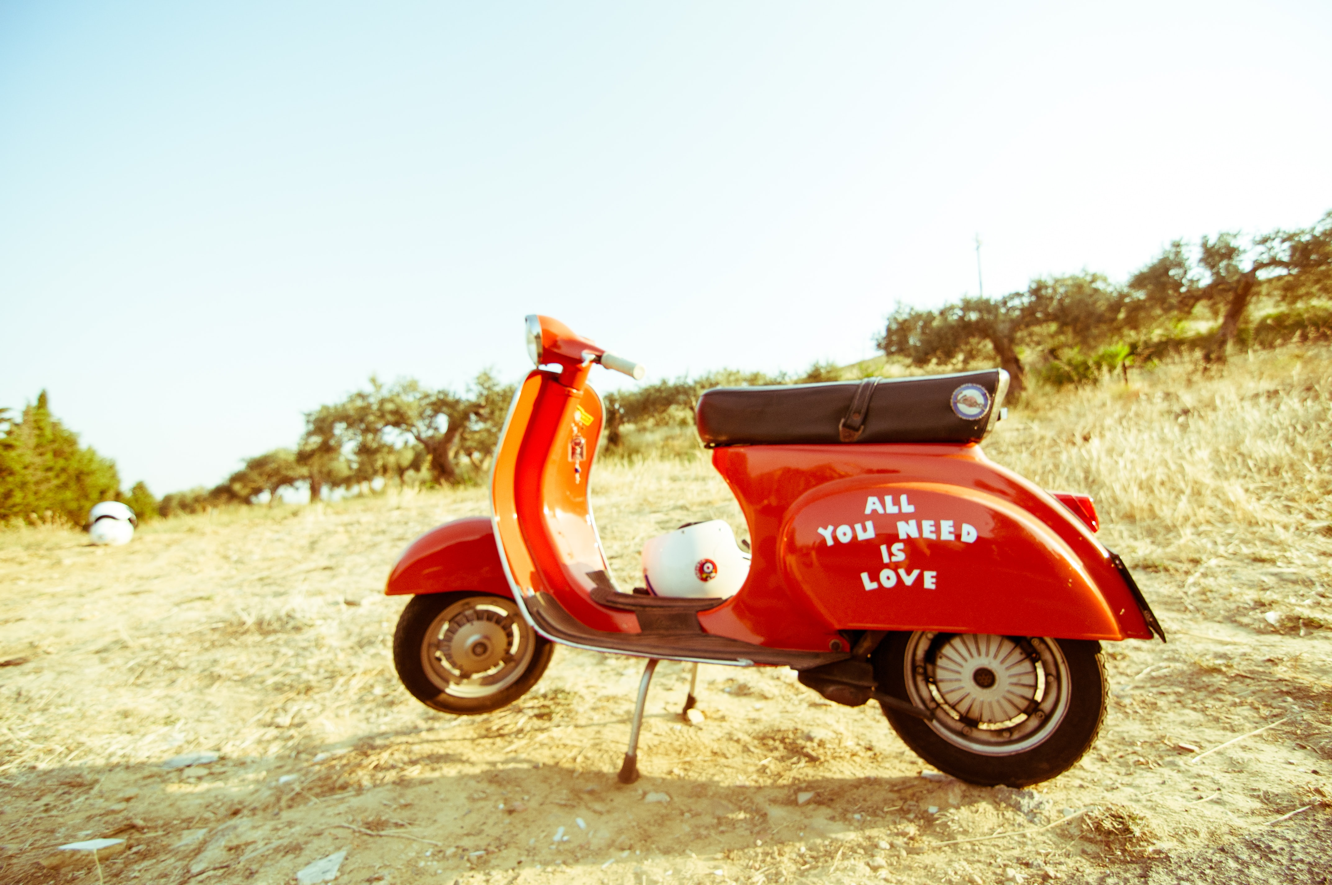 "A motorscooter reading ""ALL YOU NEED IS LOVE"" sits a dry grassy area in Caltagirone"