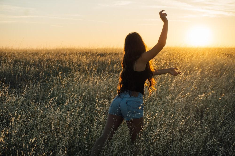 woman dancing at green grass field during sunset
