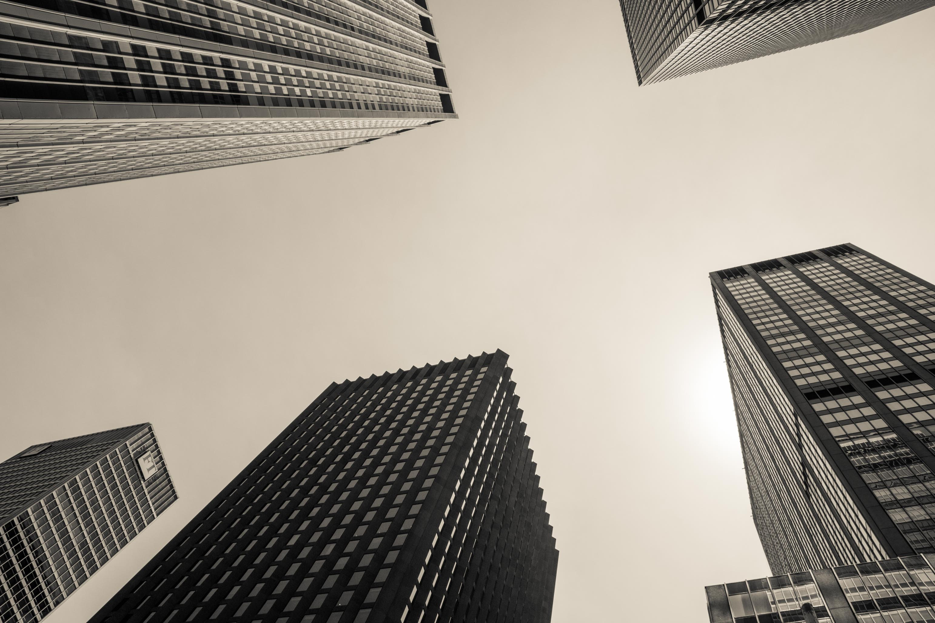 low angle and grayscale photography of high-rise buildings